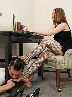 Redhead is writing an e-mail while slave is providing a footrest for her fet