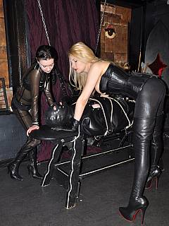 Slave is put in a rubber bag and strapped to BDSM bench with ropes so girls could play little tortures on him