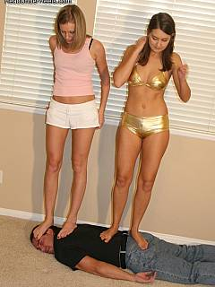 Barefoot girlfriends are having lots of fun walking and trampling a man
