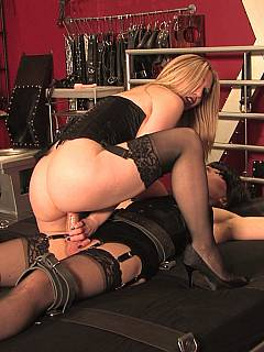 Feminized slave is strapped to bed with BDSM restraints and having a gorgeous woman on top of him: teasing cock with her wet and slippery pussy