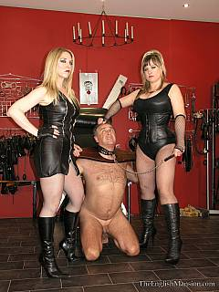 MILF girlfriends are both wearing sexy black leather when tormenting man with wooden BDSM stocks and painful foot kicks