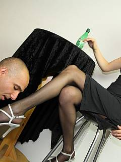 Posh babe is enjoying drinks while her sexy legs in nylons and high heel shoes are worshipped by the collated sub