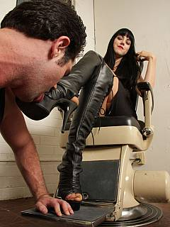 The passion of submission is revealed by the slave licking fashionable leather knee boots his mistress is wearing