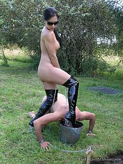 Leggy Goddess is using her sexy feet o to push collared slave down into the mud bath