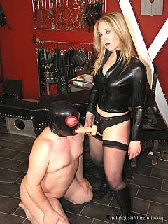 Hot babe in black leather is making slave happy by pushing big vibrating strap-on into his ass doggy style