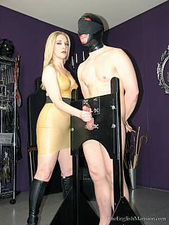 Femdom stops being funny when mistress in latex locks you and your cock into wooden BDSM stocks, deny your orgasms and makes you swallow her saliva