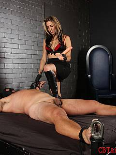 Hot babe is gagging exposed male with the rubber cock to silent him a bit while she is tormenting his balls