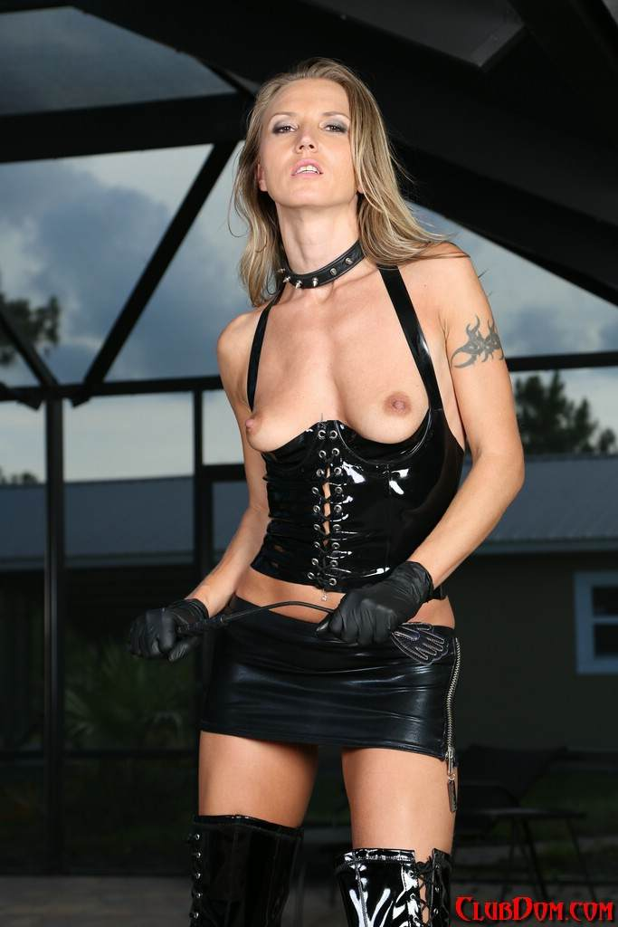 Picture #3 of Slim babe is all dressed up for femdom action: wearing PVC lingerie and a pair of knee-boots