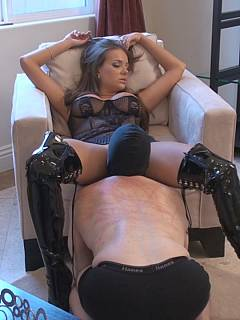 Mistress is relaxing in the chair while kneeling sub is licking her in between her spread legs
