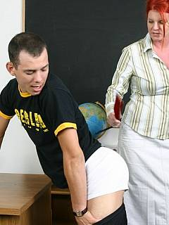 Naughty schoolboy gets a few painful spanks over his exposed ass from the sexy ILF teacher