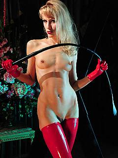 Mistress is mastering the whip being all naked but wearing red latex stockings and heels