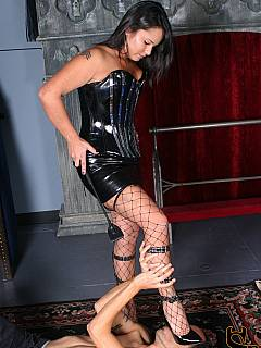 Mistress in black fishnets is going on with the trampling after slave worshiped her feet