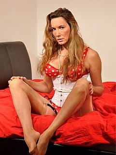 Erotic mistress is wearing kinky red polka-dot set of lingerie with a pair of tan nylon stockings