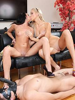 Male slave becomes sex toy for a couple of horny gals: armed with the cock-gag he has to satisfy both of the dommes