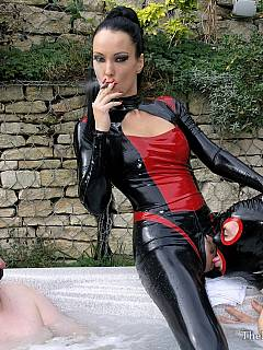 Goddess in latex is enjoying a hot tub with two slaves: smoking a cigarette and making masked subs swallow the ash