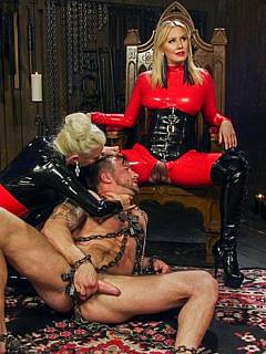Man is taken down and tortured by a team of two gorgeous femdom ladies in latex catsuits armed with strap-on cocks