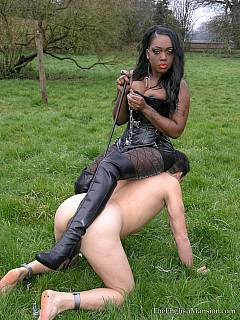 Petboy on the stroll: black babe is dragging collared male slave by the leash across the filed