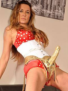 Dominatrix is showing off kinky combination of polka-dot clothing and a golden sex toy to degrade men with