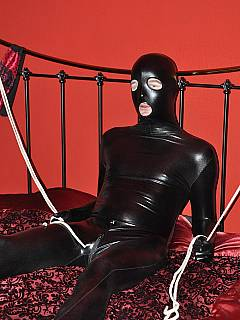 Sissy trainee is dressed up in PVC catsuit and taking strap-on into his throat as if he is a real slut