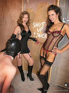 Kneeling slave is becoming a sissy by serving a cock in the gloryhole under the guidance of a couple of hot dommes