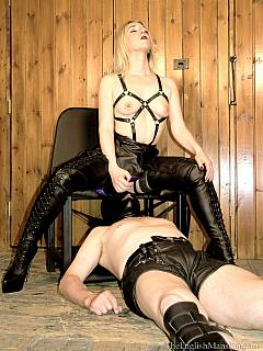Queening mistress looking very sexy in kinky BDSM harness: sitting on her throne and humiliating femdom slave with shaved cunt