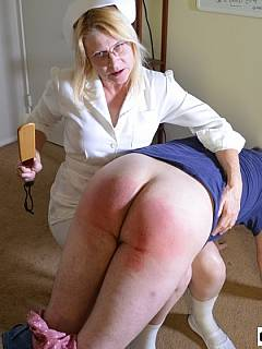 Mature nurse is wearing her uniform when using paddle to make man suffer pain and make his ass bright red