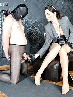 Miserable sissy is kneeling in front of gorgeous dominatrix: wearing pantyhose and with his penis locked into chastity cage