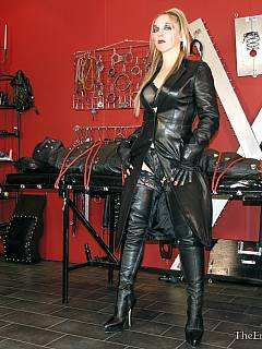 Hot babe loves leather: wearing black costume herself and keeping the cock-teased slave in leather body-bag