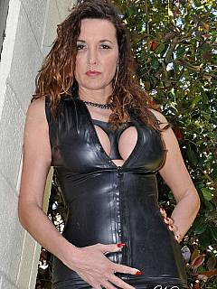 MILF dominatrix is showing off her latest fetish outfit: short rubber dress that comes along nicely with black stockings