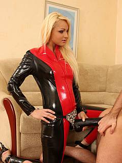 Bitchy blond in PVC cat-suit is having a gigantic strap-on cock to destroy male asses with