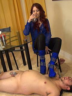 Redhead is enjoying a new foot rest for her spike heel boots in form of naked and cock-caged femdom slave