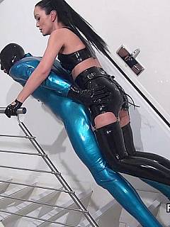Anal slave is taking big strap-on in his ass while he and his mistress are both wearing kinky rubber outfits