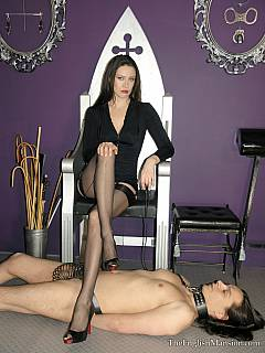 Classy dominatrix is subjecting femdom slave to oral discipline: fucking his mouth with strap-on while strapped helplessly with leather belts