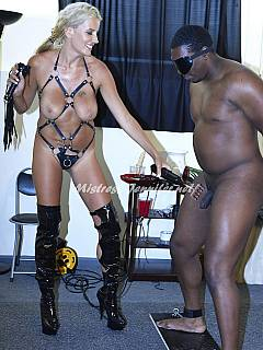 White dominatrix is getting ready to humiliate black slave: dressing up in sexy leather harness and takes a whip in her hands