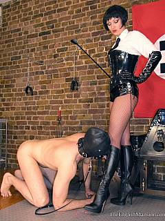 Kneeling submissive is cleaning up military bitch's leather boots with licking after they were stained with cum