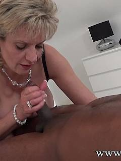 Busty mature babe is using her mouth to tease the black slave: sucking his cock and denying the ejaculation