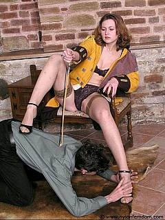 Dude is floored and enjoying a facesitting session with a domme wearing black panties and a pair of nylon stockings