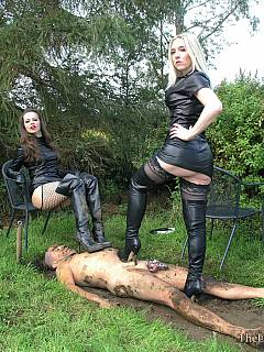 Posh ladies in high heel knee boots are having fun pushing naked male into the dirt and them forcing him lo lick clean their shoes