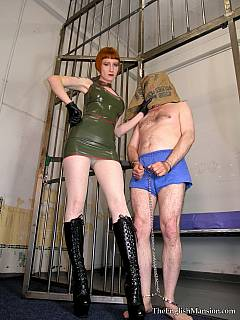 Redhead military bitch is wearing latex in the scene where she is interrogating a man in prison cell