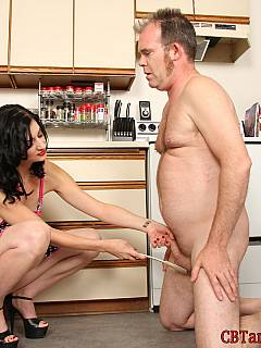 Naked housewife is only wearing an apron when tormenting small penis slave with different types of household objects