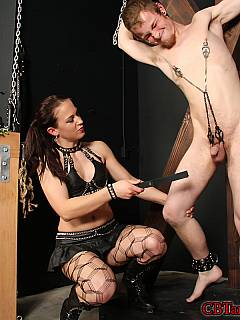 BDSM cross is holding naked slve firmly while his exposed cock is beaten up with wooden cane