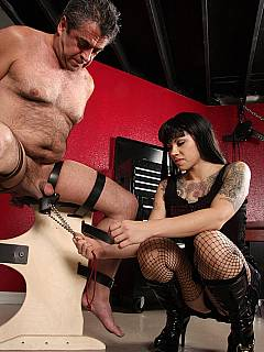 Belted to the BDSM chair, this naked sub is forced to sit with his legs spread when lead weights attached to unprotected balls