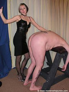 Naked punk is bent over the BDSm rack and having his exposed ass slapped by elegant blond