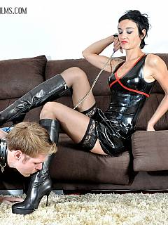 Lady in rubber is testing slave licking skills on the boots and then making him worship her ass