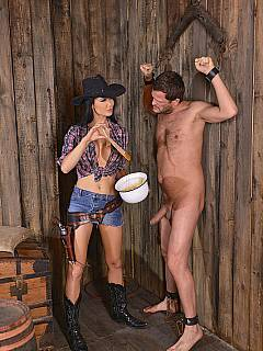Horny cowgirl is tormenting and fucking handcuffed slave in the barn threatening him with the gun
