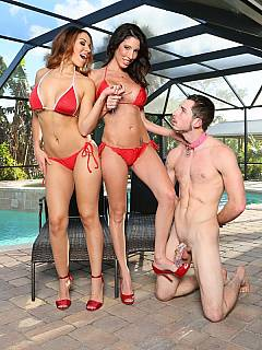 Male slave is locked into chastity tube and serving a couple of stunning women in red bikini