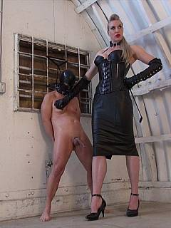 Tall dominatrix is using riding crop to control masked femodm slave when teaching him masturbate on command
