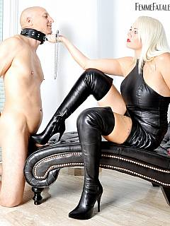 Collared slave is kneeling in front of the gorgeous mistress in leather dress and knee-boots receiving a bit of sexy trampling