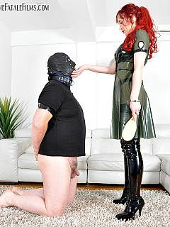 Fat guy with small penis is kneeling in anticipation waiting to be paddled by a leggy Goddess in latex dress