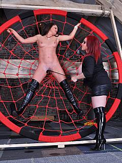 Lesbian is put into the middle of spiderweb for whipping and canning lesson by the domme with big juicy boobs
